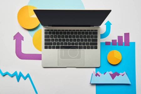 Photo for Top view of opened laptop, charts and graphs, pointers made of paper on white background - Royalty Free Image