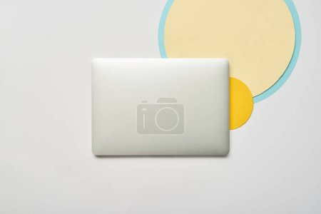 Foto de Vista superior de la portátil cerrado y círculos de papel sobre fondo blanco - Imagen libre de derechos