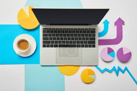 Photo pour Vue du dessus de l'ordinateur portable, tasse de café et cartes et graphique papier, pointeurs, feuilles de papier sur fond blanc - image libre de droit