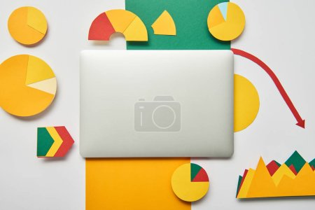 top view of paper charts and graphs, pointers, sheet of paper and laptop on white background