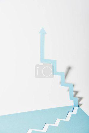 Photo for Paper arrow upward on white and blue background - Royalty Free Image