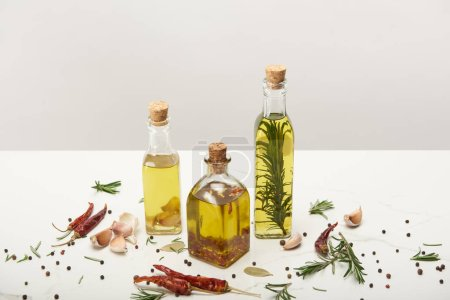 Photo for Various bottles of oil flavored with different spices and rosemary on white surface - Royalty Free Image