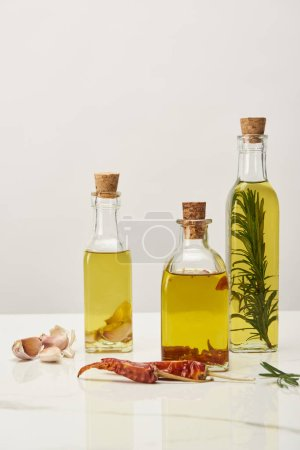 Photo for Different bottles with oil flavored with various spices and rosemary on white surface - Royalty Free Image