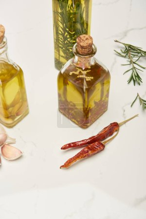 Photo for Corked bottles of oil flavored with rosemary and different spices on white surface - Royalty Free Image