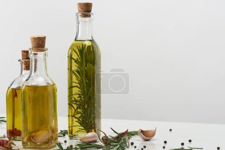 Photo for Different bottles of oil flavored with various spices and rosemary on white surface - Royalty Free Image