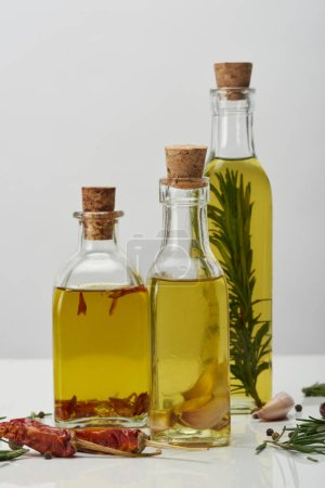 Photo for Bottles of oil flavored with rosemary and various spices on white surface - Royalty Free Image