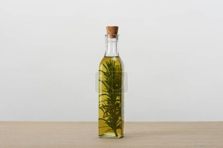 Photo for Corked bottle of flavored oil with rosemary branch inside on grey surface - Royalty Free Image