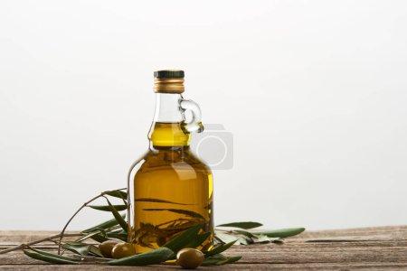 Photo pour Bouteille d'huile avec feuilles d'olivier et olives isolées sur gris - image libre de droit