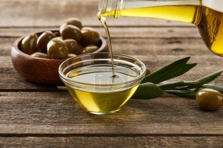 Photo pour Verser l'huile de la bouteille dans un bol en verre, un bol d'olives, une branche d'olivier et une olive sur une surface en bois - image libre de droit
