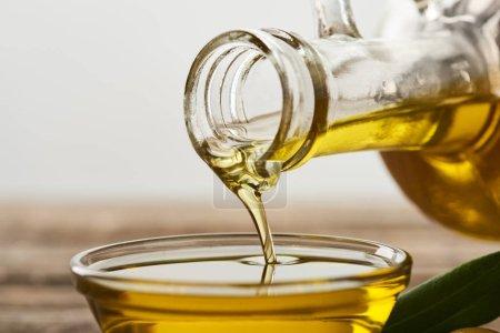 Photo pour Verser l'huile d'olive de la bouteille dans un bol en verre sur fond gris - image libre de droit