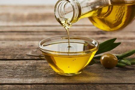 Photo pour Verser l'huile de la bouteille dans un bol en verre, feuilles d'olivier et d'olive sur la surface en bois - image libre de droit