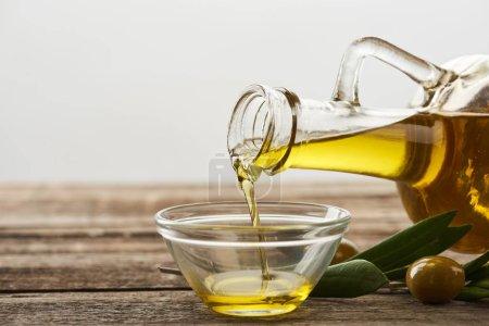 Photo pour Verser l'huile de bouteille dans bol en verre, les feuilles d'Olivier et les olives sur la surface en bois - image libre de droit