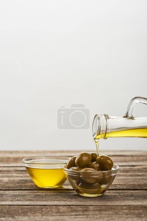 Photo for Pouring of into glass bowl with olives, and bowl full of oil on wooden surface - Royalty Free Image