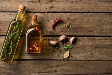 Photo for Top view of bottles of oil flavored with different spices and rosemary on wooden surface - Royalty Free Image