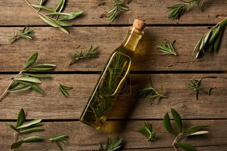 Photo for Top view of bottle with flavored oil and rosemary branches on wooden background - Royalty Free Image