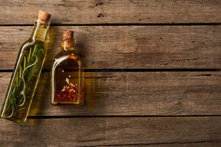 Photo for Top view of bottles with oil flavored with rosemary and spices on wooden background - Royalty Free Image