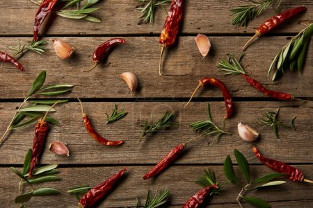 Photo for Top view of chili peppers, rosemary branches and garlic cloves on wooden background - Royalty Free Image