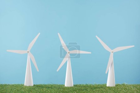 white windmill models on grass and blue background