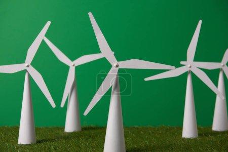 Photo pour Modèles de moulin à vent blanc sur gazon et fond vert - image libre de droit