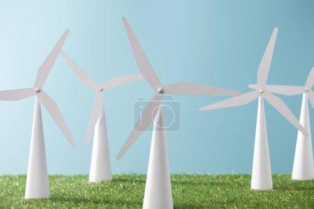 Foto de Modelos de molino de viento blanco en fondo azul y verde hierba - Imagen libre de derechos
