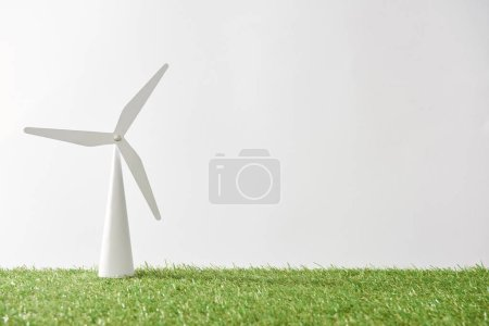 windmill model on green grass and white background with copy space