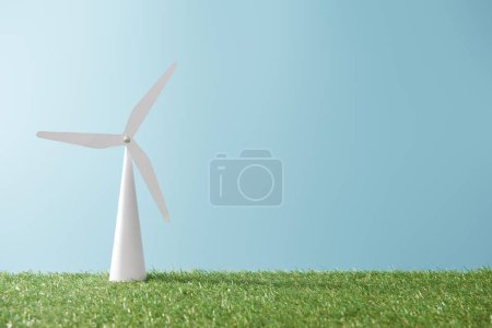 windmill model on green grass and blue background with copy space