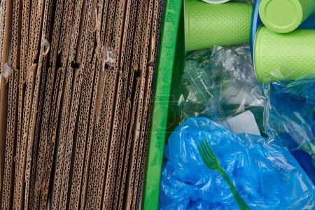 Photo pour Vue du dessus des poubelles avec carton, sacs en plastique froissés, gobelets et fourchettes en plastique - image libre de droit