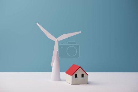 Foto de Molino de viento y casas modelos en mesa blanca y fondo azul - Imagen libre de derechos