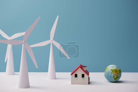 windmill and house models with small globe on white table and blue background