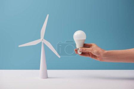 Foto de Vista recortada de la mujer sosteniendo la bombilla sobre la mesa blanca con el modelo de molino de viento sobre fondo azul - Imagen libre de derechos