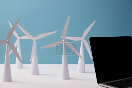 laptop on white table with windmill models on blue background