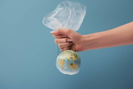 Photo pour Vue recadrée de la femme tenant globe dans un sac transparent en plastique sur fond bleu - image libre de droit