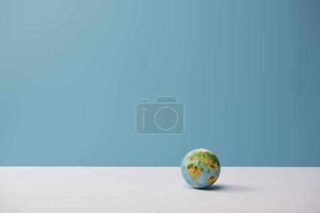 Photo pour Petit globe sur tableau blanc et fond bleu - image libre de droit