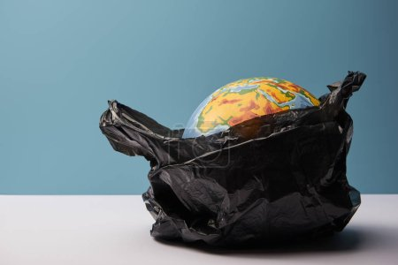 Photo for Globe in black polyethylene bag on white table and blue background - Royalty Free Image