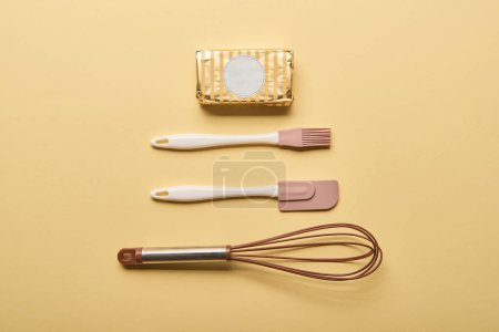 Photo for Flat lay with butter, balloon whisk, spatula and bakery brush on yellow background - Royalty Free Image