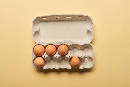 Photo for Top view of brown organic eggs in cardboard box on yellow background - Royalty Free Image