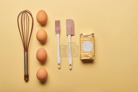 Photo for Flat lay with balloon whisk, eggs, spatula, bakery brush and butter on yellow background - Royalty Free Image