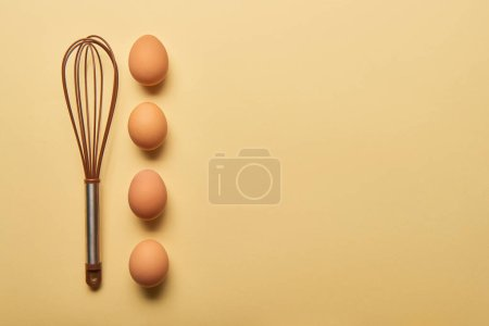 top view of balloon whisk and eggs  on yellow background
