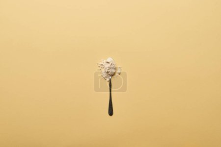Photo for Top view of spoon with scattered flour on yellow background - Royalty Free Image