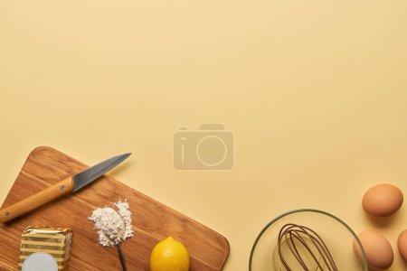 Draufsicht auf Zutaten und Messer auf Holzschneidebrett auf gelbem Hintergrund