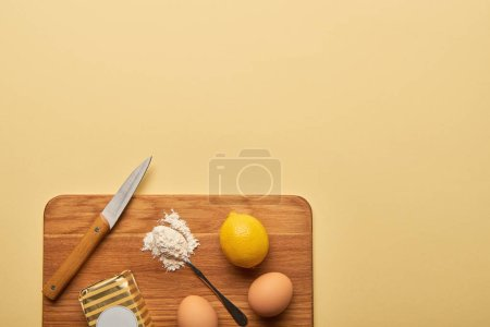 Photo for Top view of ingredients and knife on wooden chopping board on yellow background with copy space - Royalty Free Image