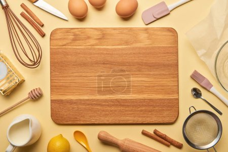 Photo for Top view of empty wooden chopping board with cooking utensils and ingredients on yellow background - Royalty Free Image