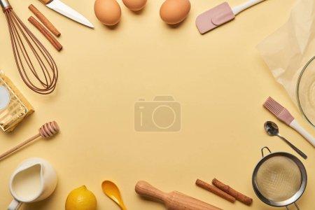 Kochutensilien und Zutaten von oben auf gelbem Hintergrund mit Kopierraum