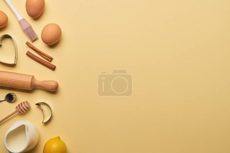 Photo for Top view of bakery ingredients and cooking utensils with dough molds on yellow background with copy space - Royalty Free Image