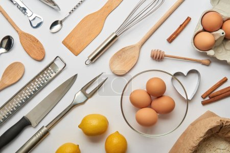 Photo for Flat lay with metal and wooden cooking utensils and raw products on grey background - Royalty Free Image