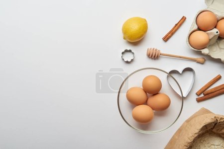 Photo for Top view of bakery ingredients and dough molds on grey background - Royalty Free Image