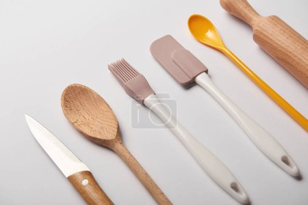 Photo for Cooking utensils arranged in row on grey background - Royalty Free Image