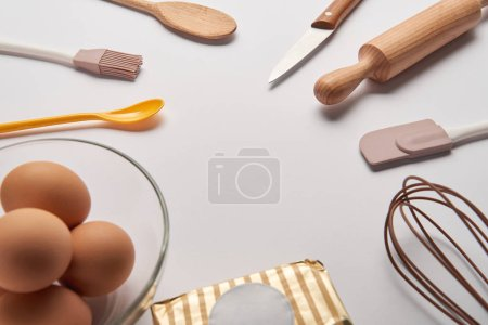 Photo for Cooking utensils, butter and eggs in bowl on grey surface - Royalty Free Image