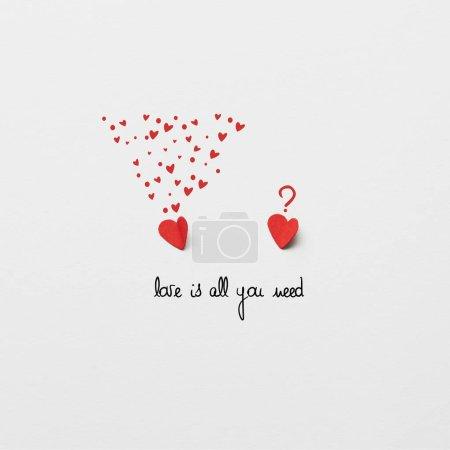 """Photo for Top view of two red paper cut hearts on white background with """"Love is all you need"""" lettering - Royalty Free Image"""