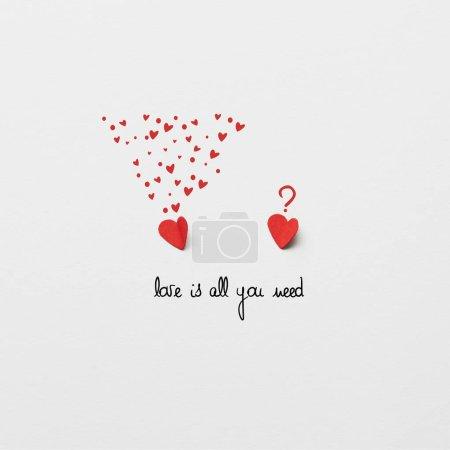Photo pour Vue de dessus du papier rouge deux coupe des coeurs sur fond blanc avec «Love is all you need» lettrage - image libre de droit